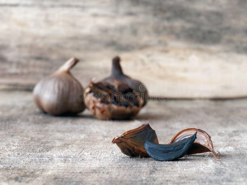 Jäste svarta vitlökkulor och kryddnejlikor arkivbild