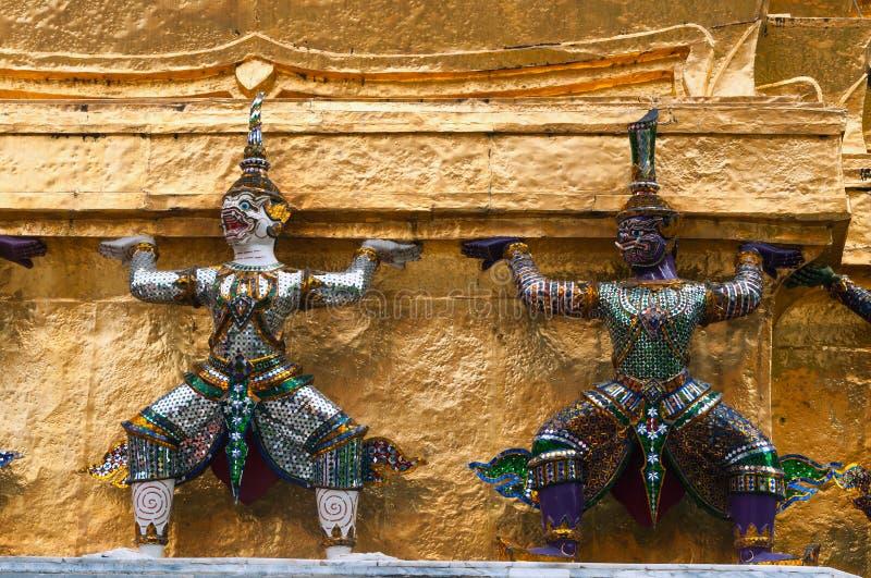Jätte- demonförmyndarestatyer på guld- Chedi av Wat Phra Kaew bangkok storslagen slott thailand royaltyfri fotografi