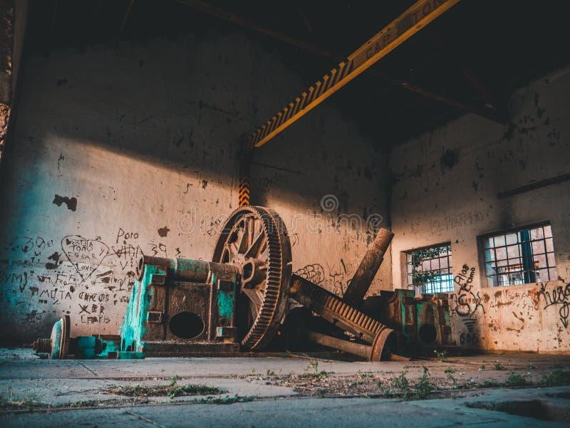 Jätte- gamla rostiga kugghjul i slumpmässig handstil för gammalt lager på väggen royaltyfri fotografi