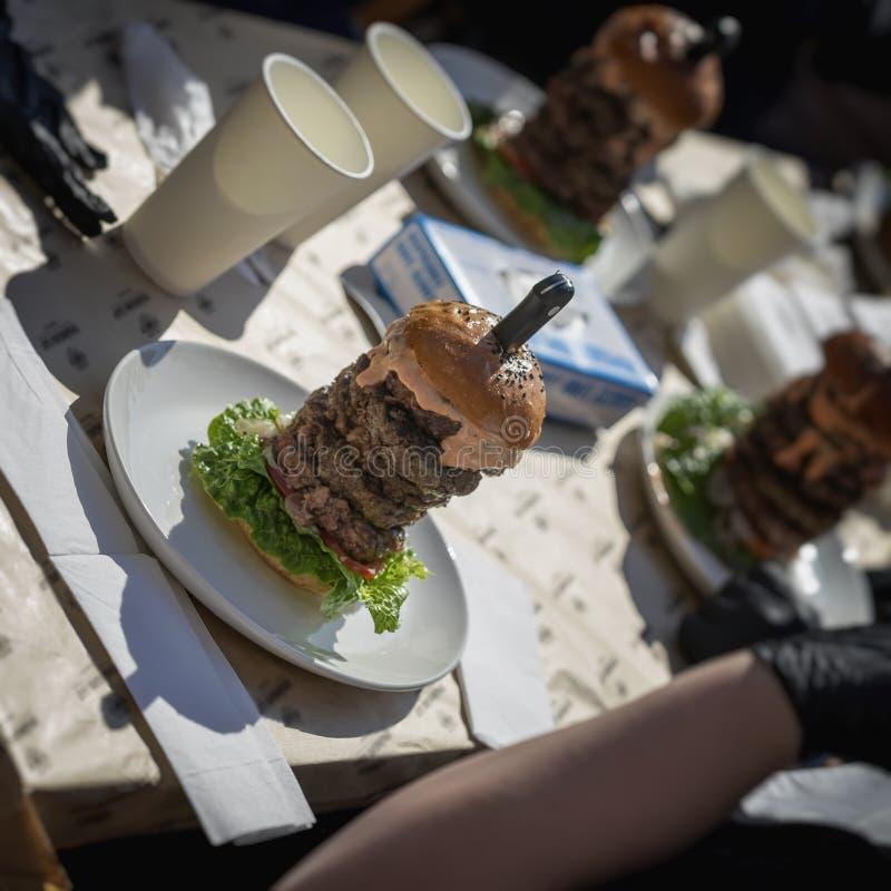 Jätte- hamburgare för de, som kan ` t få nog, stor hamburgare - för läckra verkliga fans och ny mat Gastronomisk gourmet royaltyfri bild