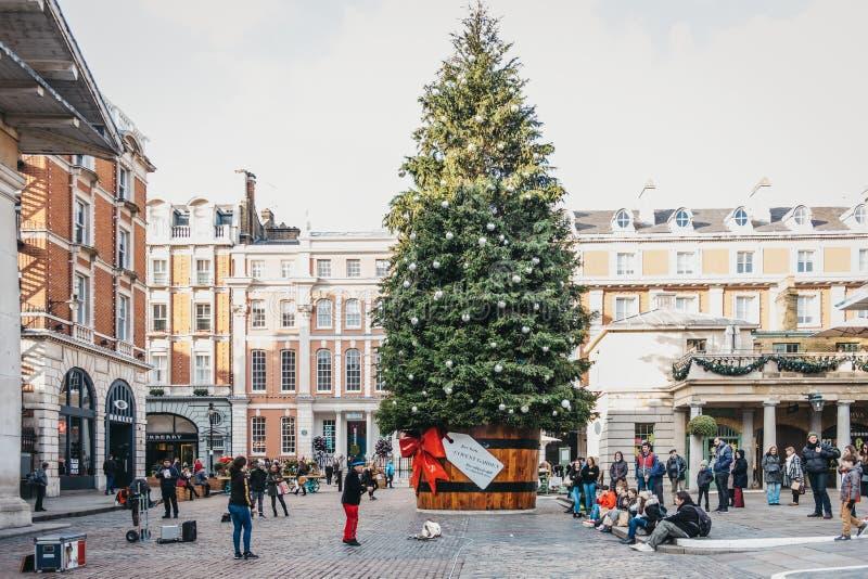 Jätte- julgran i en kruka med en gåvaetikett framme av den Covent Garden marknaden, London, UK royaltyfri bild