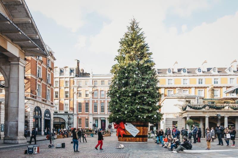 Jätte- julgran i en kruka med en gåvaetikett framme av den Covent Garden marknaden, London, UK arkivfoto