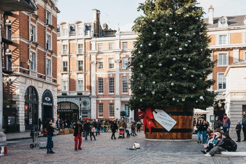 Jätte- julgran i en kruka med en gåvaetikett framme av den Covent Garden marknaden, London, UK arkivbilder