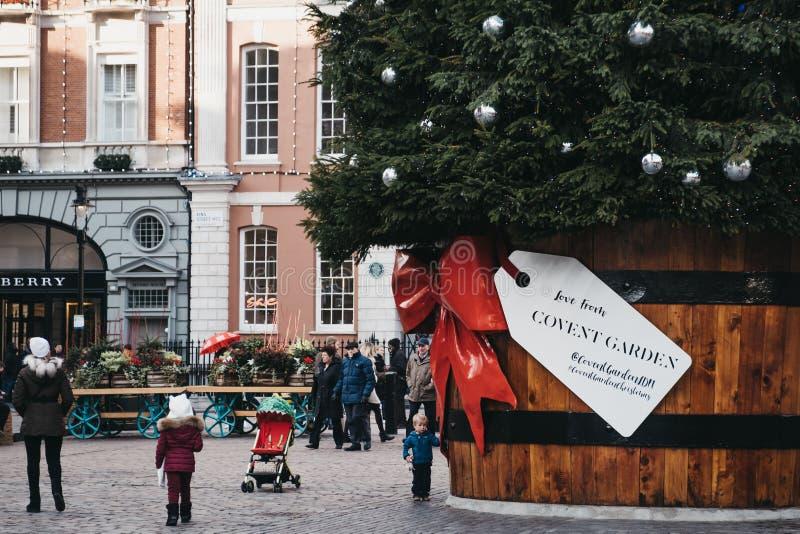 Jätte- julgran med en gåvaetikett i den Covent Garden marknaden, London, UK royaltyfri bild