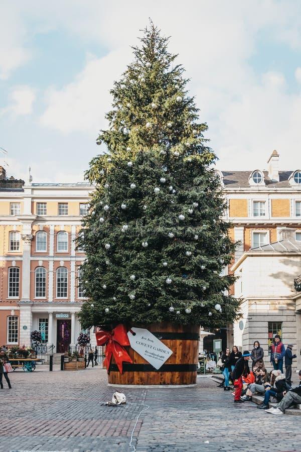 Jätte- julgran med en gåvaetikett i den Covent Garden marknaden, London, UK arkivfoto