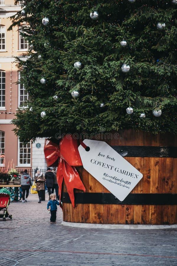 Jätte- julgran med en gåvaetikett i den Covent Garden marknaden, London, UK arkivbilder