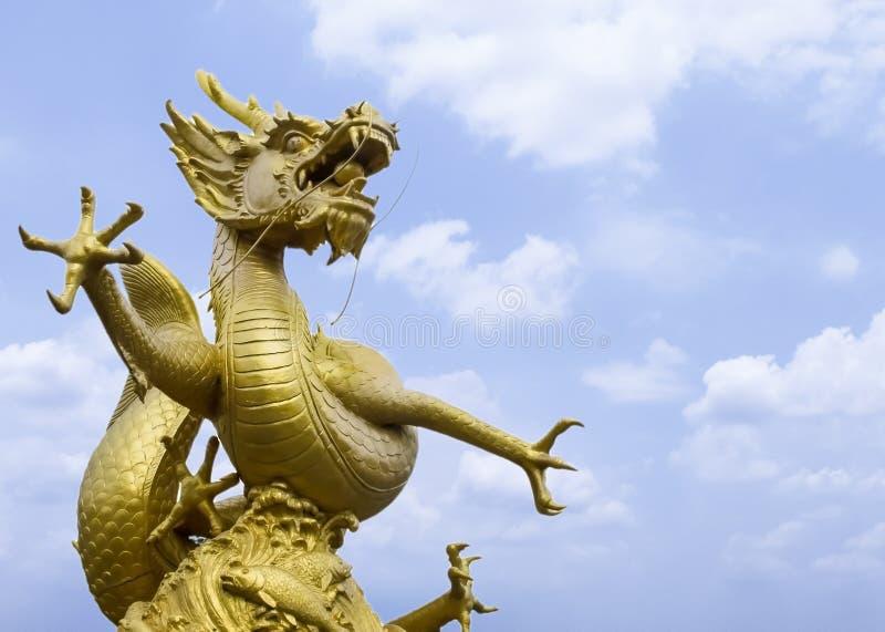 Jätte- kraftiga guld- Dragon Statue på hörnet med blå himmel och molnet i bakgrund fotografering för bildbyråer