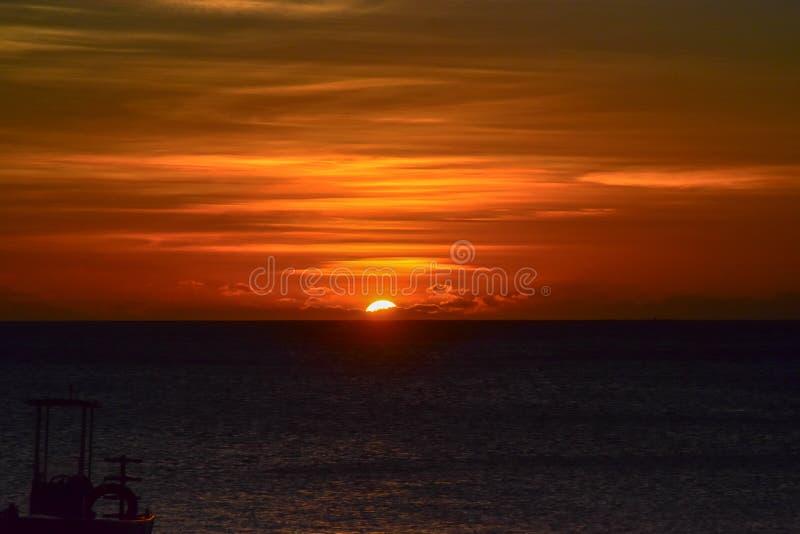 Jätte- orange solinställning in i havet med skugga av fiskebåten royaltyfri foto
