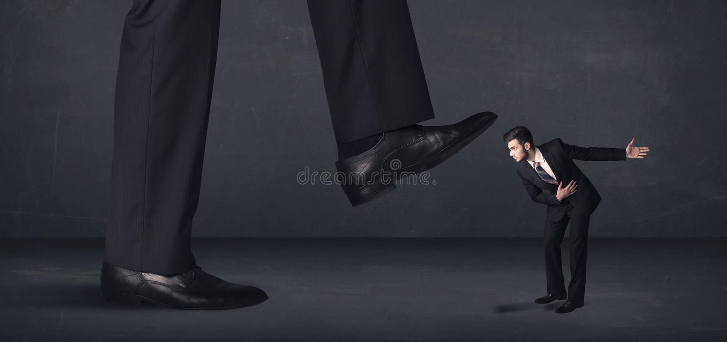 Jätte- person som lite kliver på affärsmanbegrepp arkivbild