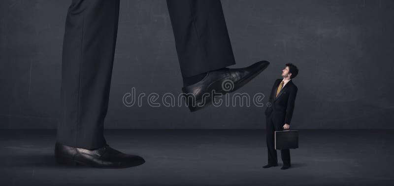 Jätte- person som lite kliver på affärsmanbegrepp arkivfoto