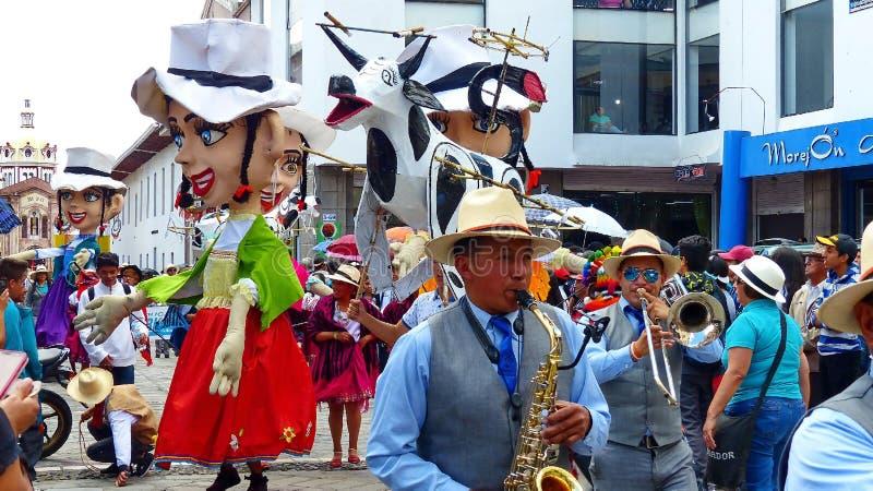 Jätte- skyltdockor, folk dansare och 'galet kraxar 'på ståtar, Ecuador arkivfoto