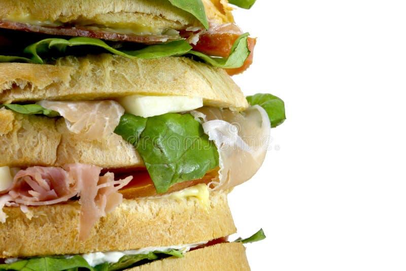 Jätte- smörgås som är välfylld med många lager av bröd med grönsallat till fotografering för bildbyråer