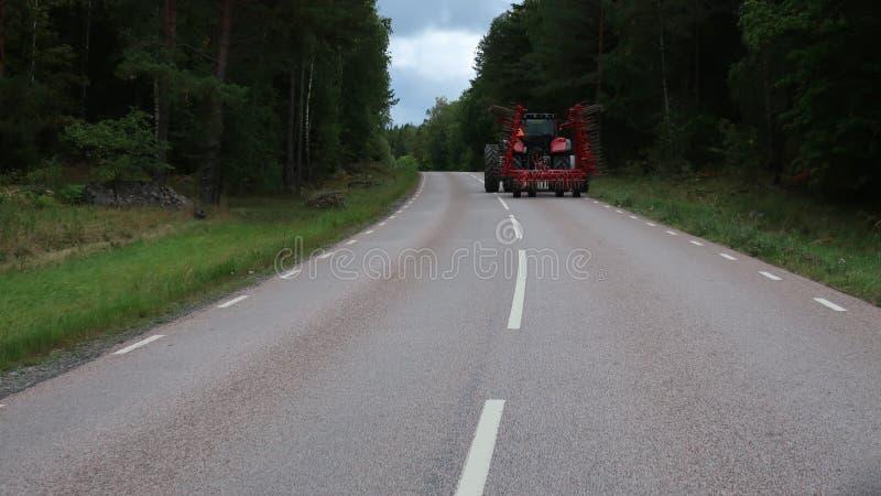 Jätte- traktor på vägen royaltyfri fotografi