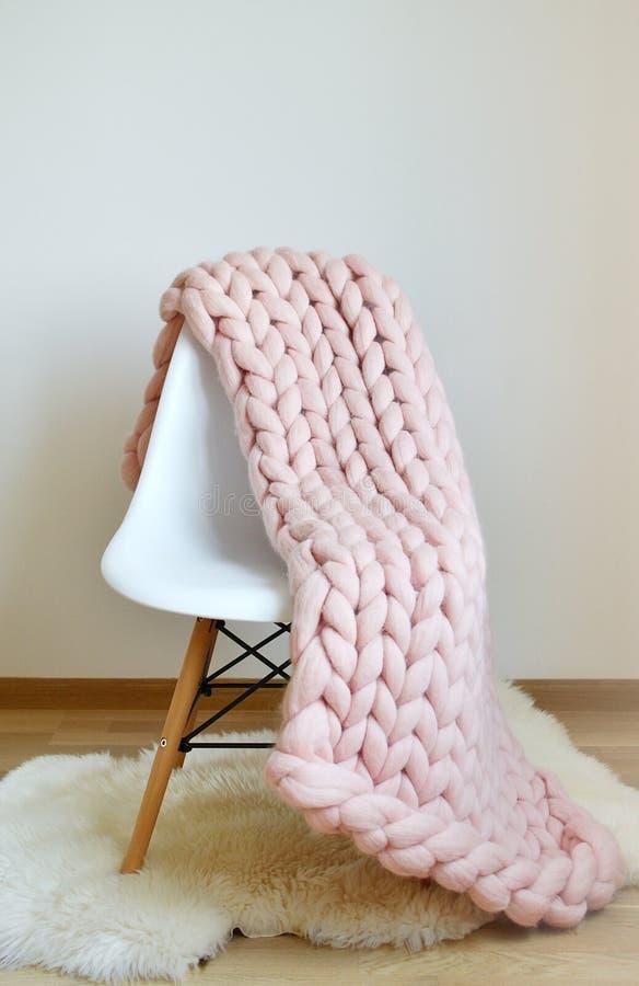 Jätte- Woolen för rosa färgfilt som stickas på vit trästolstol arkivfoto