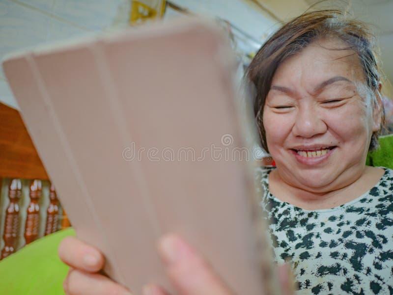 Jätteglade gamla asiatiska kvinnor ser minnestavlan i hennes hus royaltyfria bilder