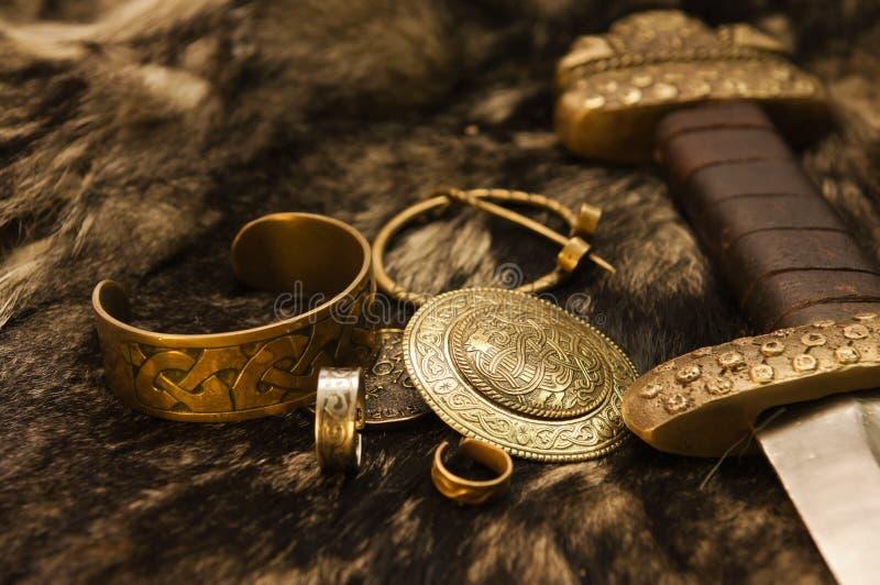 Jóias e espada escandinavas em uma pele imagem de stock