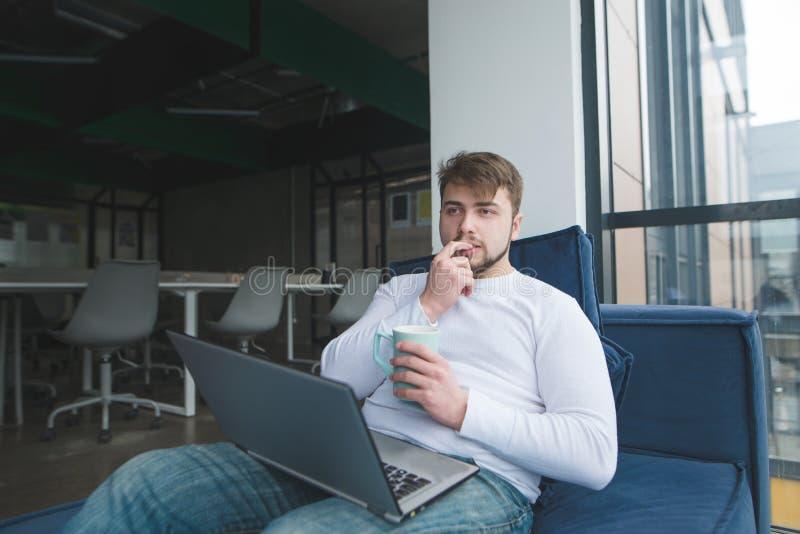 Jóvenes con un ordenador portátil y una taza de bebida caliente que se sientan en el sofá y el pensamiento imagen de archivo