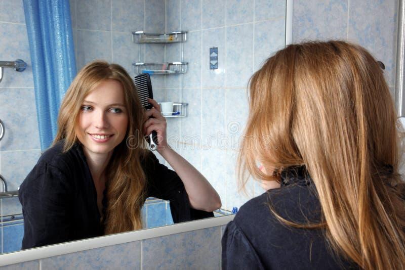 Jóvenes de un espejo que corrige los pelos imagenes de archivo