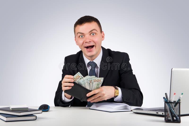Jóvenes divertidos que gritan al hombre de negocios caucásico acertado en el traje negro que sostiene el dinero imagenes de archivo