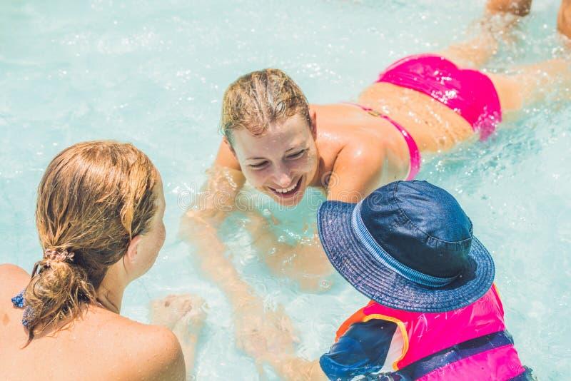 Jóvenes felices dos mujeres y muchacho que juegan y que tienen un buen rato en la piscina del parque de la diversión del agua, en imagenes de archivo