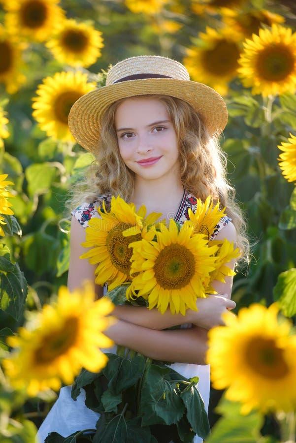 Jóvenes hermosos en el campo de girasoles imagen de archivo