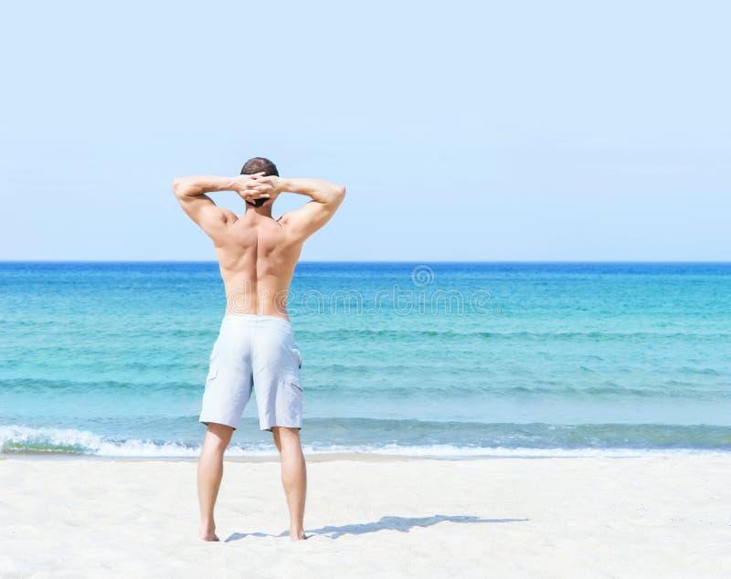 Jóvenes, hombre apto que se coloca en una playa del verano foto de archivo