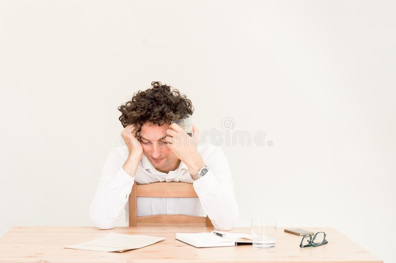 Jóvenes, hombre caucásico cansado del freelancer que se sienta en su Ministerio del Interior en la tabla delante de la pared clar imagenes de archivo
