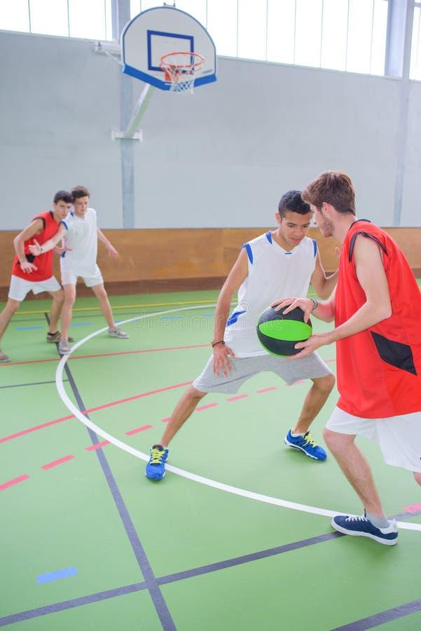 Jóvenes jugando baloncesto imágenes de archivo libres de regalías