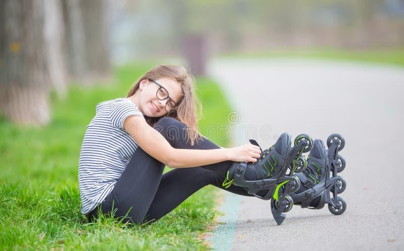 Jóvenes lindos que van rollerblading sentarse en la hierba que pone en inlin foto de archivo