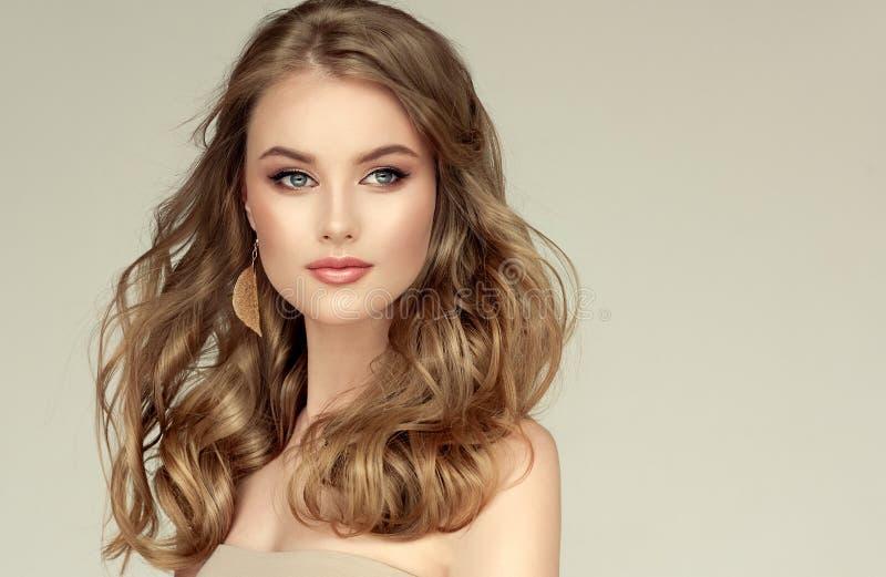 Jóvenes, modelo hermoso cabelludo rubio con el pelo largo, bien preparado, vestido en pendientes de oro Peinado libremente de col imágenes de archivo libres de regalías