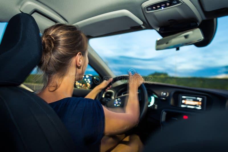 Jóvenes, mujer que conduce un coche en la oscuridad foto de archivo