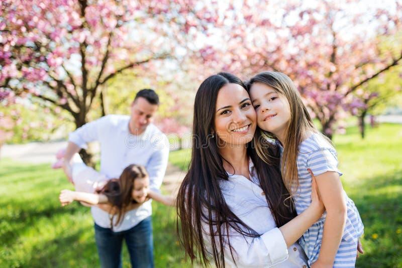 Jóvenes padres con pequeños hermanos parados afuera en la naturaleza primaveral foto de archivo