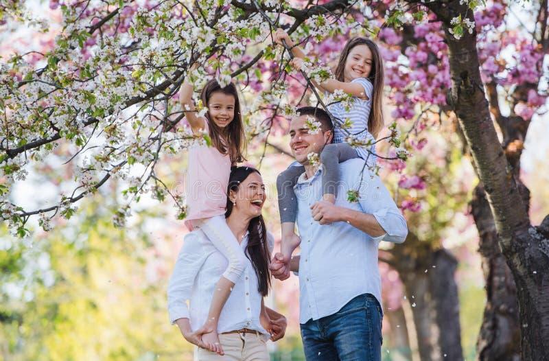 Jóvenes padres con pequeños hermanos parados afuera en la naturaleza primaveral imagenes de archivo