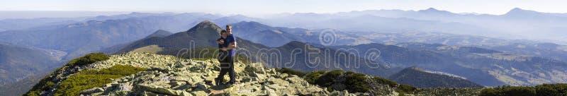 Jóvenes pareja caminan por las montañas de los Cárpatos Hombre y mujer parados en la cima de una montaña mirando el hermoso paisa imagen de archivo libre de regalías