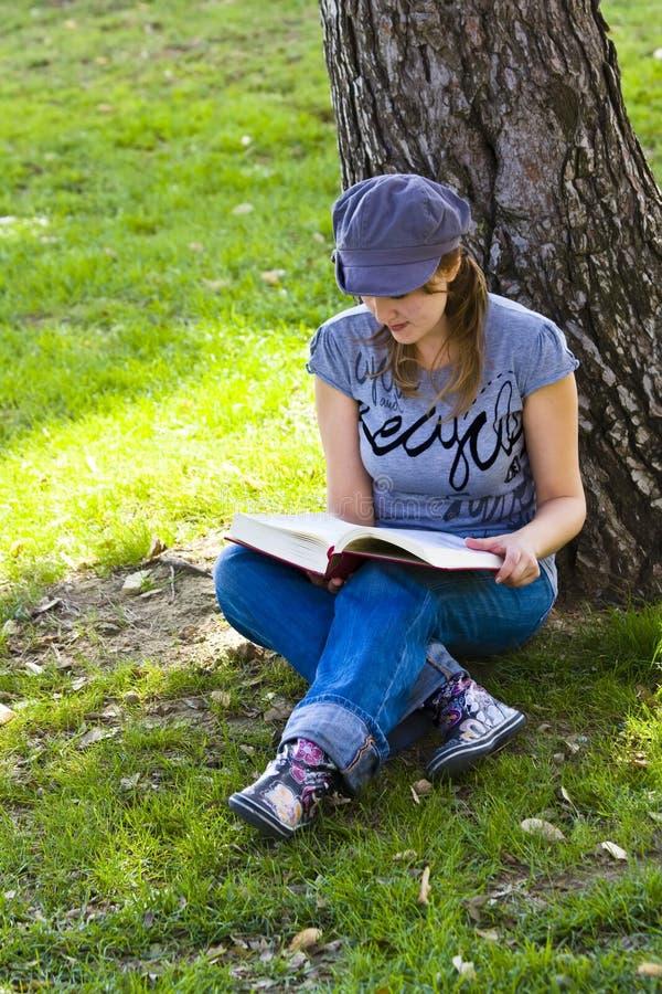 Jóvenes que gozan de un libro imagenes de archivo
