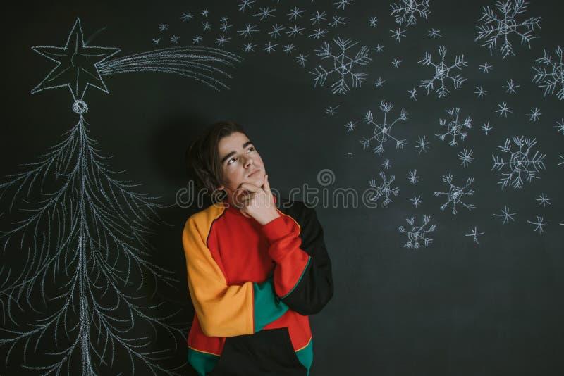 Jóvenes que piensan con la decoración de la Navidad foto de archivo libre de regalías