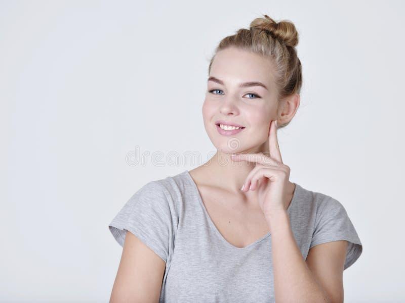 Jóvenes que piensan a la mujer caucásica con el finger cerca de cara imagen de archivo