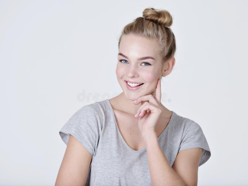 Jóvenes que piensan a la mujer caucásica con el finger cerca de cara fotos de archivo