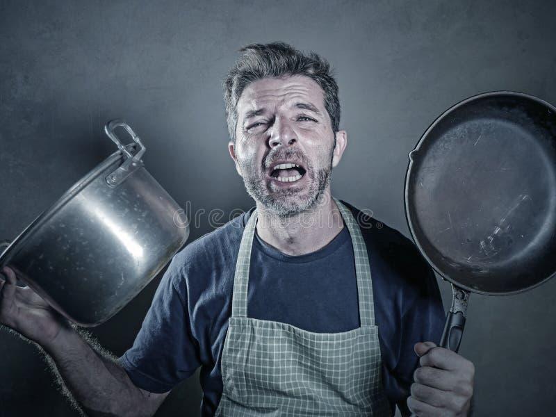 Jóvenes subrayados y hombre perezoso divertido con el delantal que sostiene la cacerola de la cocina y el pote de la cocina que g fotos de archivo libres de regalías
