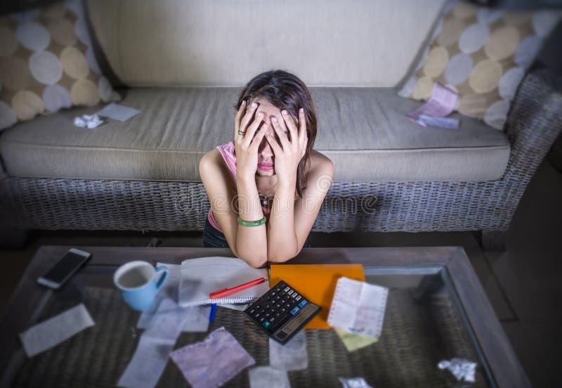 Jóvenes subrayados y tensión preocupante del sufrimiento de la mujer que calcula cuentas y deuda mensuales de los costos en favor fotos de archivo libres de regalías