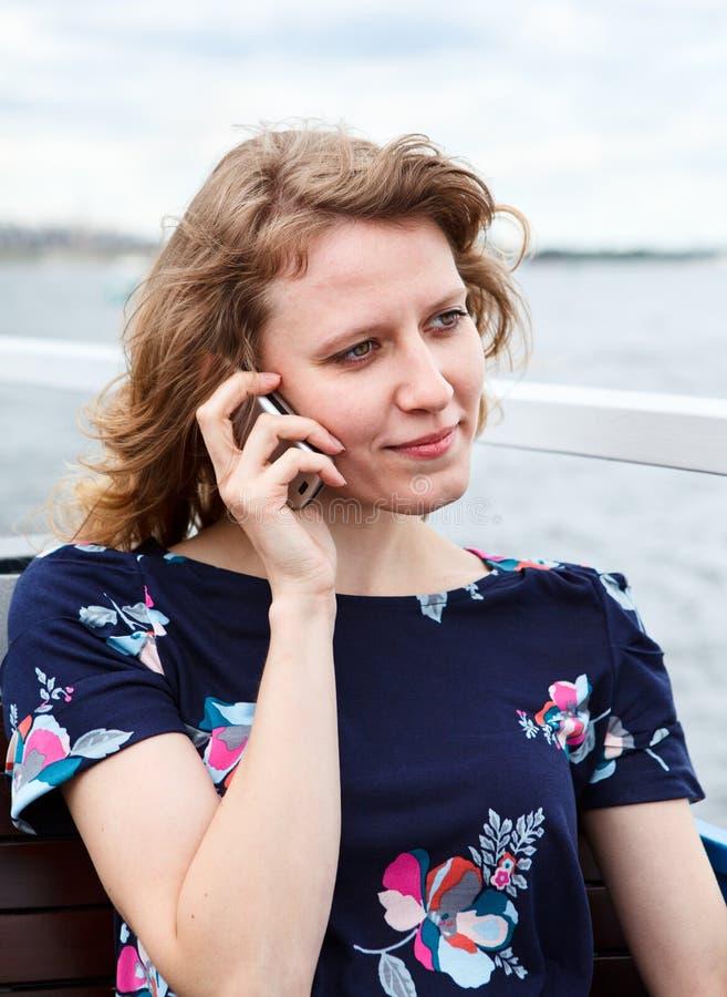 Jóvenes una mujer que invita al teléfono móvil imagen de archivo