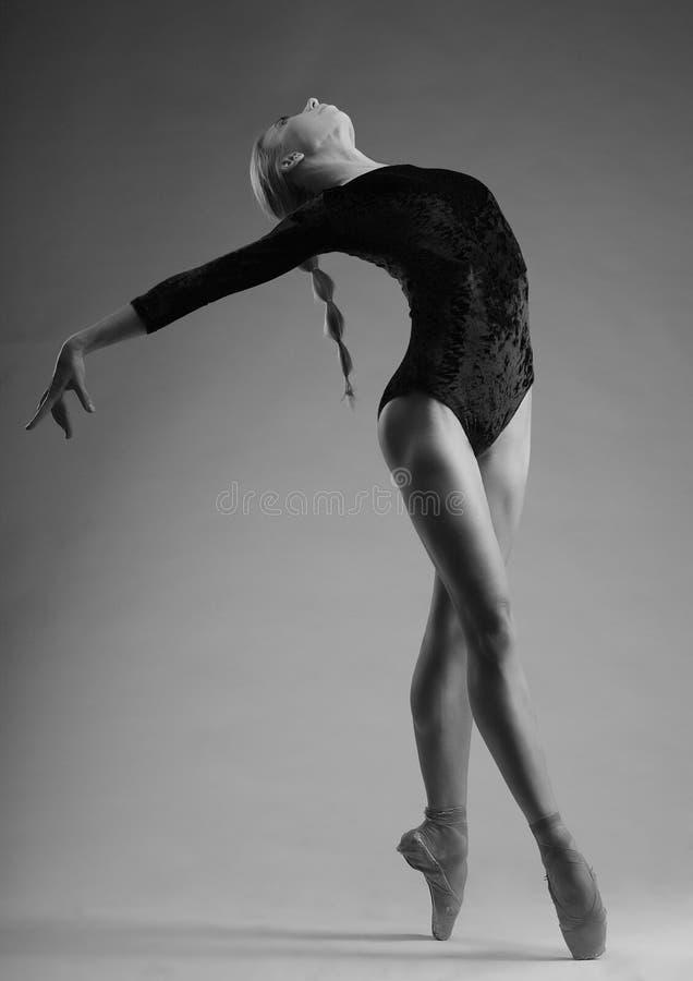 Jóvenes y bailarina increíblemente hermosa que plantean el baile en estudio actitud del ballet clásico, blanco negro de la Americ imágenes de archivo libres de regalías