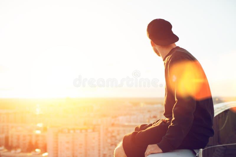 Jóvenes y hombre valiente que se sientan al borde del tejado y que miran lejos la ciudad foto de archivo libre de regalías