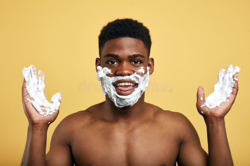 Júbilo agradable positivo del hombre en afeitar por la mañana foto de archivo