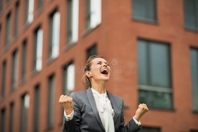 Júbilo de la mujer de negocios delante de la oficina imagenes de archivo