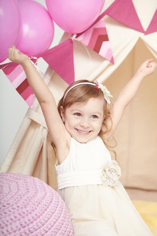 Júbilo lindo feliz de la niña en la fiesta de cumpleaños fotografía de archivo