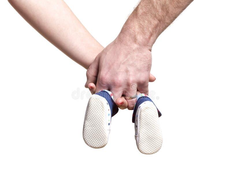 Júntese con las manos que sostienen los zapatos de bebé foto de archivo