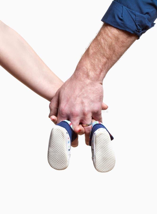 Júntese con las manos que sostienen los zapatos de bebé imágenes de archivo libres de regalías