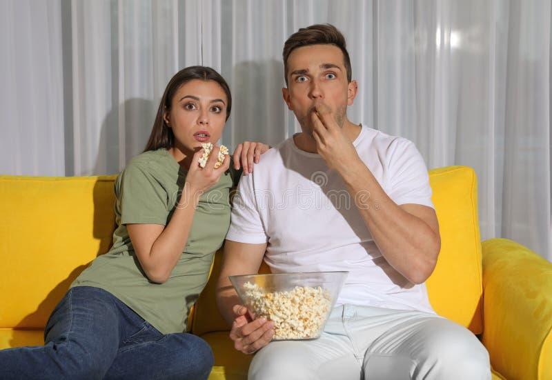 Júntese con las palomitas que ven la TV junto en el sofá fotos de archivo libres de regalías