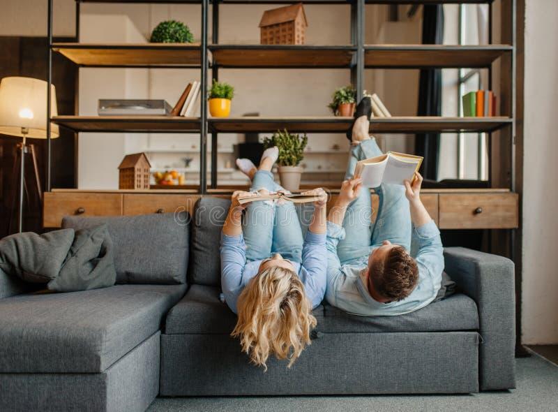 Júntese con los libros que mienten en el sofá al revés foto de archivo libre de regalías